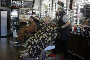 Barbers cut hair at Primo's Barbershop on Monday, May 4, 2020, in Vacaville, Calif. Juan Desmarais, owner of Primo's Barbershop, re-opened his business on Friday, May 1, 2020, after realizing it could be months before he had permission to operate due to COVID-19 restrictions. (AP Photo/Ben Margot)