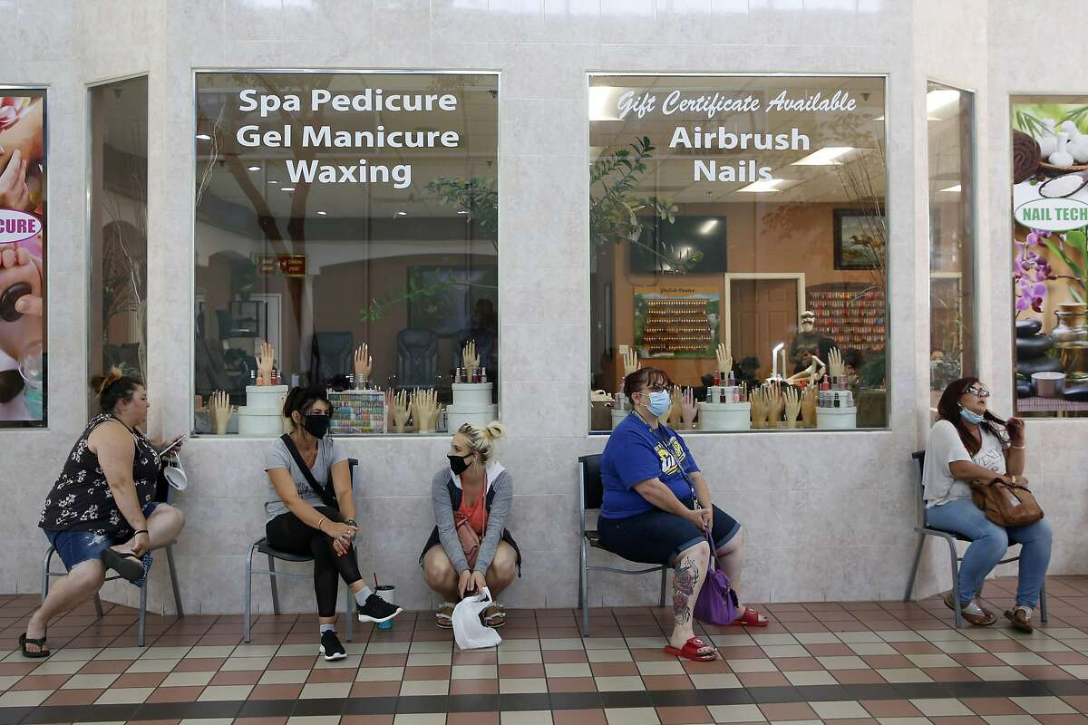 FILE - In this May 6, 2020, photo customers wait to get their nails done at the Nail Tech salon in the Yuba Sutter Mall in Yuba City.