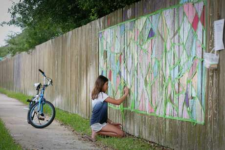Viviana Luna, 11, takes part in a chalk mosaic community art project on a fence in theStonebridgeneighborhood Friday, April 3, 2020, in Pearland. Luna said she misses her friends, but taking part in the neighborhood art project makes her feel good.