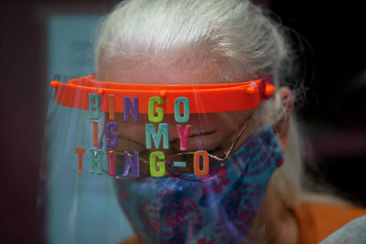 """Alamo Hills Daytime Bingo employee Linda Pieniazek wears a face shield that reads """"Bingo is my thing-o"""" as she works at the bingo hall. Bingo halls reopened on Friday per state guidelines at 25 percent capacity with social distancing."""