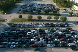 Vehicles line up as the Community Assistance Center distributes food to 500 families at The Ark Church, Wednesday, April 15, 2020, in Conroe. On May 30, the CAC will be having another food market at Milstead Automotive in Spring with enough food for 300 families.