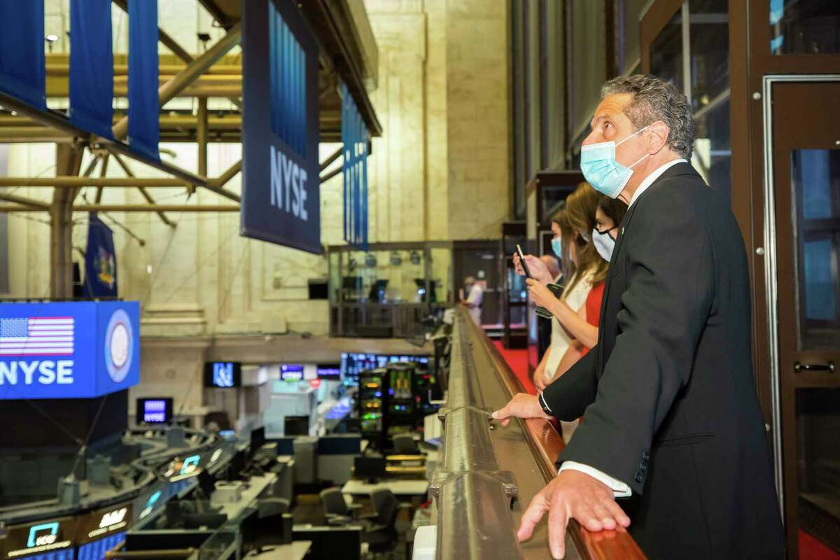 In this image provided by the New York Stock Exchange, New York State Gov. Andrew Cuomo looks over the floor of the New York Stock Exchange, Tuesday, May 26, 2020, in New York. Gov. Cuomo rang the opening bell at the NYSE Tuesday, which allowed a limited number of traders back to the floor. It required that traders adhere to social distancing guidelines and wear masks. (Colin Ziemer/New York Stock Exchange via AP)