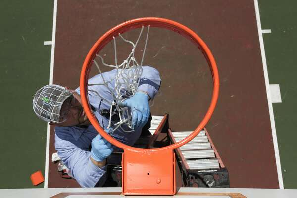 Conroe Parks and Recreation employee Pena installs a rim for the basketball court at Flournoy Park, Tuesday, May 26, 2020, in Conroe. City crews will reinstall 30 basketball hoops across the city over the next several days after they were taken down to encourage residents to avoid large gatherings and reduce the spread of COVID-19.