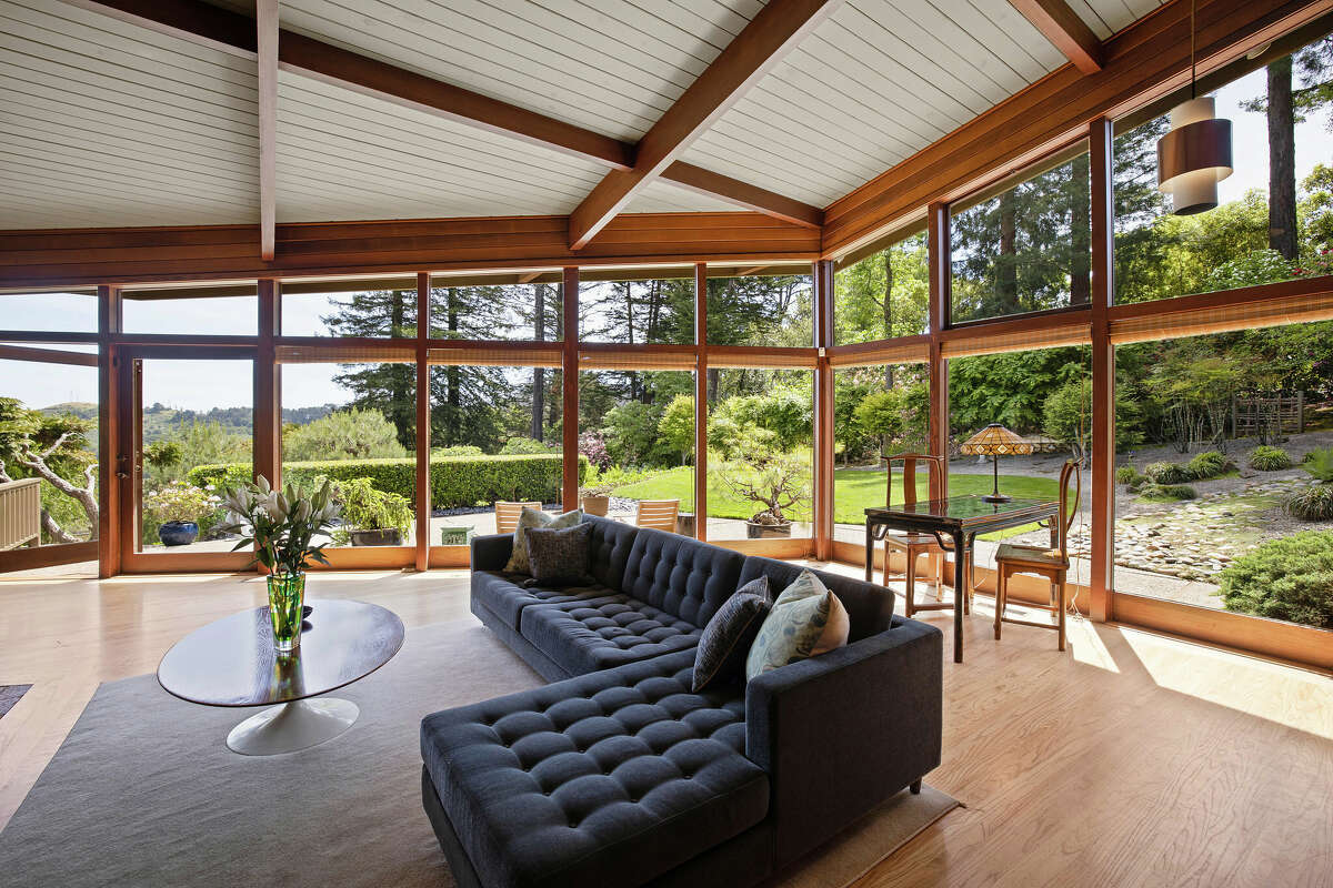 The living room is surrounded by glass for an indoor-outdoor vibe.