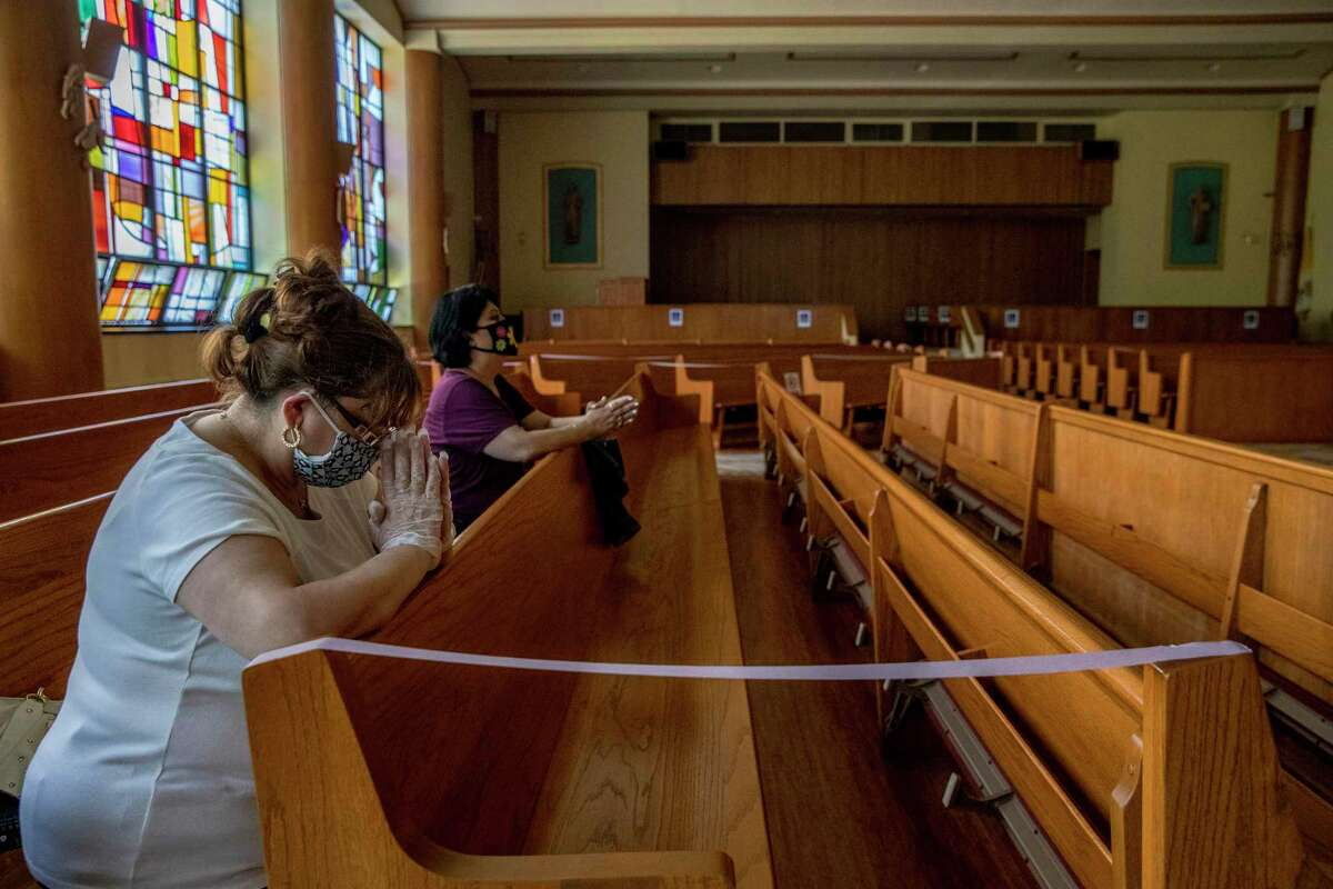 Darlene Terrezza, left, and Mireya Lonks, wearing face masks, pray at the Church of Saint Mel in Queens, N.Y., on Tuesday, May 26, 2020. Under rules on religious gatherings set last week by New York Gov. Andrew Cuomo, no more than 10 people will be allowed inside at any time, and parishioners must maintain distances of at least six feet and wear masks.