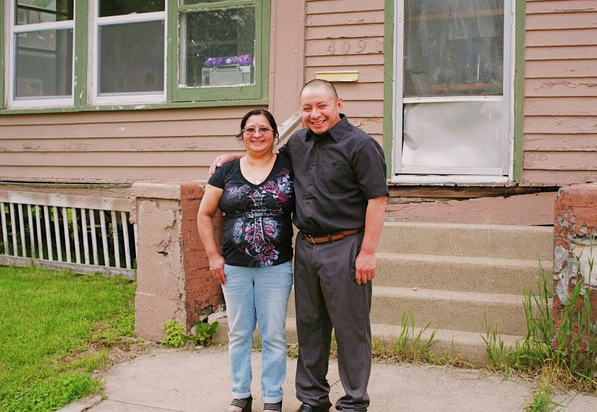 In this Saturday, May 23, 2020, photo provided by Cristobal Francisquez, his parents Paulina and Marcos Francisco pose for a photo in front of their house in Sioux City, Iowa. They bought the home after years of working in a meatpacking plant and other food processing jobs. (Cristobal Francisquez via AP)