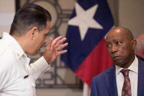 Mayor Sylvester Turner speaks to Fire Chief Samuel Peña after announcing the opening of the City of Houston's first drive-thru testing site at a news conference on Friday, March 20, 2020 in Houston.