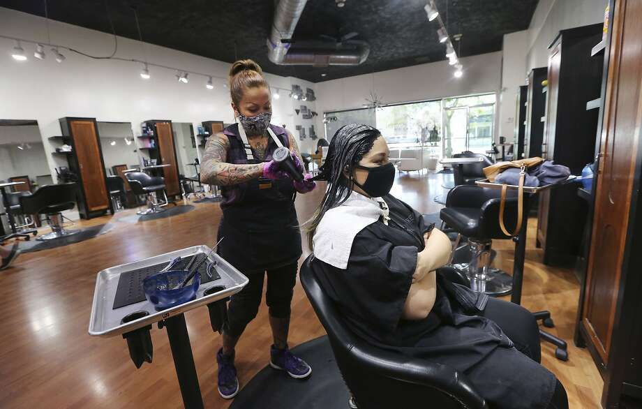 FILE - In this May 19, 2020 file photo Stylist Sandra Serrano colors client Norma Beltran's hair at the Atomic Kitten Salon in Bakersfield, Calif. Gavin Newsom cleared barbershops and hair salons to open Tuesday, May 26, 2020, in the majority of counties, the latest move in his rapid relaxation of restrictions put in place two months ago to battle the coronavirus pandemic. (Alex Horvath/The Bakersfield Californian via AP,File) Photo: Alex Horvath, Associated Press