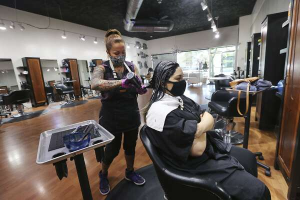 FILE - In this May 19, 2020 file photo Stylist Sandra Serrano colors client Norma Beltran's hair at the Atomic Kitten Salon in Bakersfield, Calif. Gavin Newsom cleared barbershops and hair salons to open Tuesday, May 26, 2020, in the majority of counties, the latest move in his rapid relaxation of restrictions put in place two months ago to battle the coronavirus pandemic. (Alex Horvath/The Bakersfield Californian via AP,File)