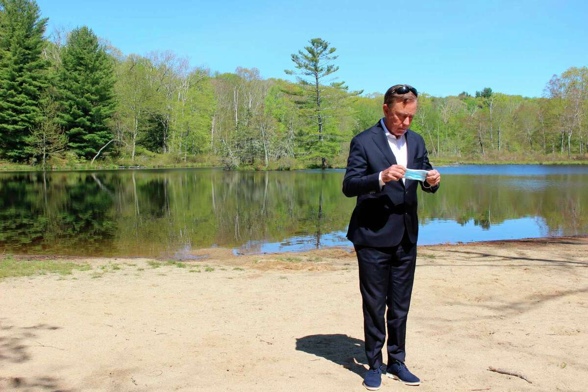 Gov. Ned Lamont prepared to put on a face mask at Gay City State Park in Hebron, in a May file photo.