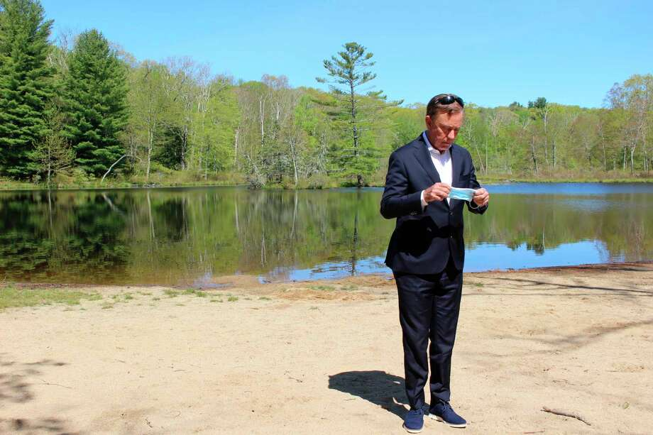 Gov. Ned Lamont prepared to put on a face mask at Gay City State Park in Hebron, in a May file photo. Photo: Pat Eaton-Robb / Associated Press / Copyright 2020 The Associated Press. All rights reserved.