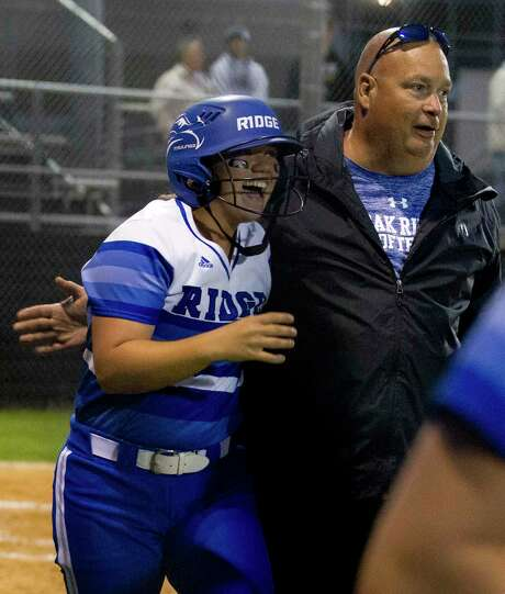 Autumn Sydlik of Oak Ridge celebrates with assistant coach James Croley after hitting a solo home run off Conroe starting pitcher Madelyn Tannery during the first inning of a District 12-6A high school softball game at Conroe High School Tuesday, March 7, 2017, in Conroe. Oak Ridge defeated Conroe 8-1. Photo: Jason Fochtman, Staff Photographer / Houston Chronicle / © 2017 Houston Chronicle