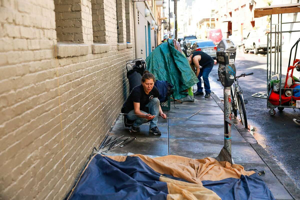 Homeless woman Wendy Novickis puts up a tent after street cleaning came through Willow Street in the Tenderloin on Wednesday, May 6, 2020 in San Francisco, California.