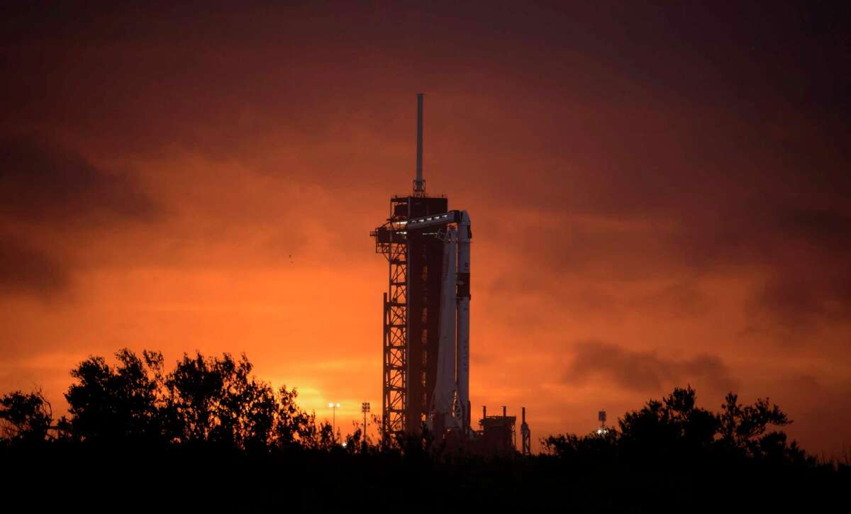 A photo provided by NASA shows a SpaceX Falcon 9 rocket with the company's Crew Dragon spacecraft onboard at Launch Complex 39A at Kennedy Space Center in Cape Canaveral, Fla., Monday, May 25, 2020, as they prepare for the Demo-2 mission. Two astronauts are scheduled to launch on May 27 for a mission to the International Space Station. (Bill Ingalls/NASA via The New York Times) -- EDITORIAL USE ONLY --