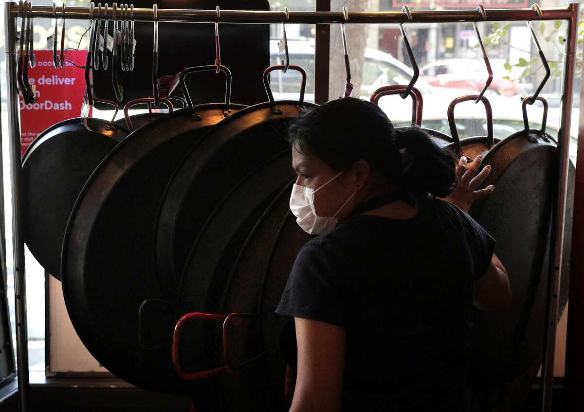 Ana Mayfield places a paella pan back on a rack in the window at restaurant La Marcha in Berkeley. Calif., on Tuesday, May 26, 2020. Owner/chef Sergio Monleon shifted his menu to include lunch offerings and takeout to stay open during the pandemic shelter in place.