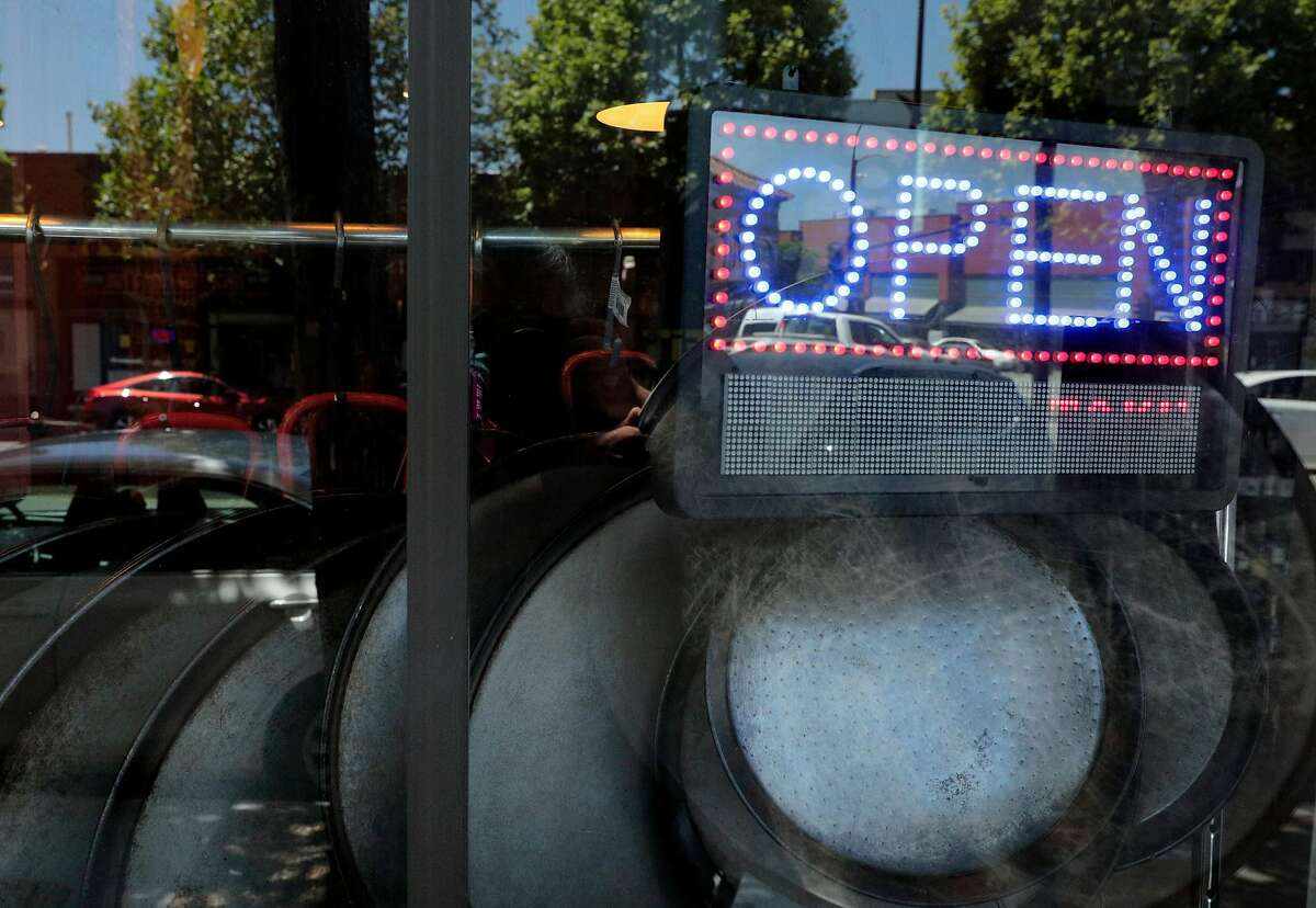 """Paella pans hang in the window beneath an """"Open"""" sign which was recently added by Sergio Monleon, owner and chef at his restaurant La Marcha in Berkeley. Calif., on Tuesday, May 26, 2020. Monleon shifted his menu to include lunch offerings and takeout."""