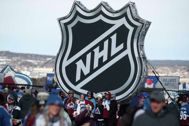 FILE - In this Saturday, Feb. 15, 2020, file photo, fans pose below the NHL league logo at a display outside Falcon Stadium before an NHL Stadium Series outdoor hockey game between the Los Angeles Kings and Colorado Avalanche, at Air Force Academy, Colo. The NHL Players' Association's executive board is voting on a 24-team playoff proposal as the return-to-play format, a person with knowledge of the situation told The Associated Press, late Thursday, May 21, 2020. (AP Photo/David Zalubowski, File)