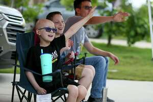 """Reagan Lee, 9, left, who recently completed his fourth and final chemotherapy treatment for stage 4 neuroblastoma, enjoys his """"End of Chemo Celebration Parade"""" with his cousin, Brandon Yarborough, 11, and brother, Alex Chavez, 16, right, in front of his family's home in Cibolo on Saturday, May 23."""