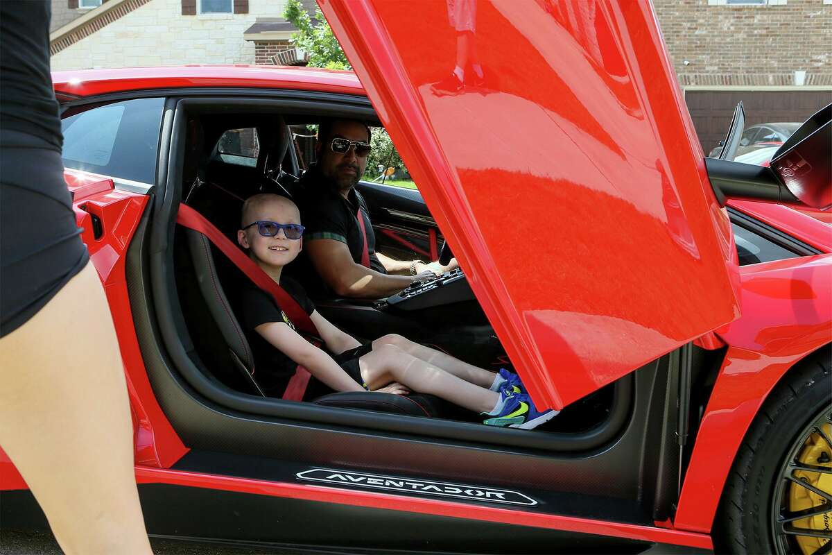 Reagan Lee, 9, who recently completed chemotherapy treatment for stage 4 neuroblastoma, is treated to a ride in Austin defense attorney Mark Hull's Lamborghini SV as part of a parade honoring the young cancer patient..