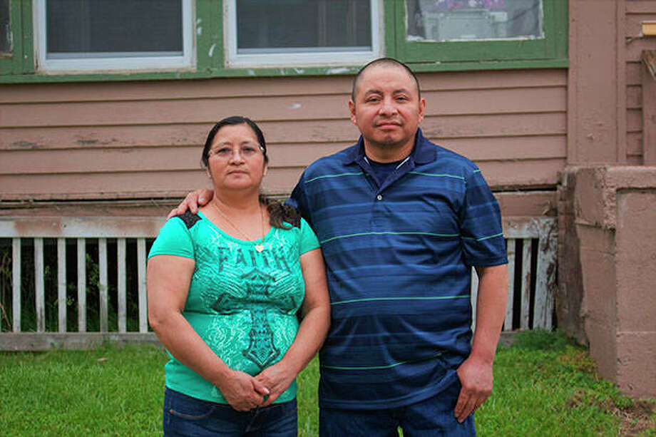Paulina and Marcos Francisco pose for a photo in front of their house. They bought the home after years of working in a meatpacking plant and other food processing jobs. Photo: Cristobal Francisquez | Via AP