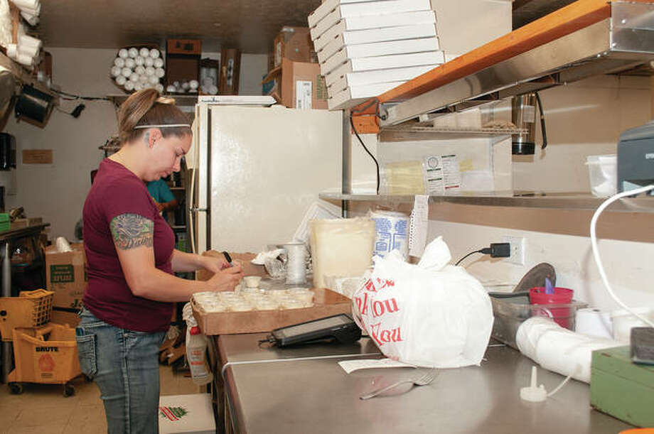 Rachel Hayes works Tuesday in the kitchen of The HandleBar Pizza and Pub. The restaurant, at 304 S. Main St., will have outdoor seating available starting Friday. Photo: Darren Iozia | Journal-Courier