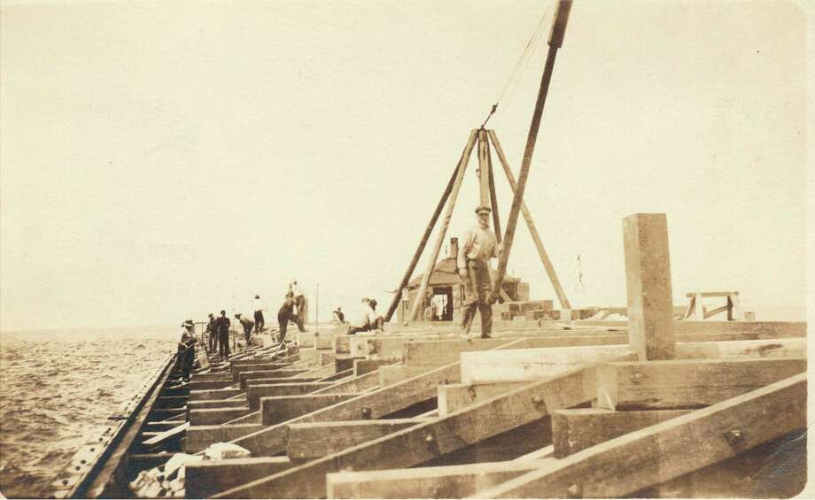Workers are shown fixing the breakwater at the beach off Manistee Harbor in this photograph from the late 1800s.