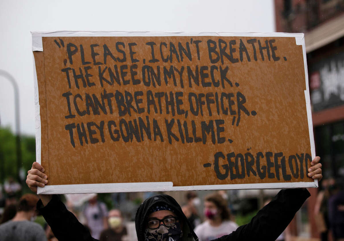 A protester holds a sign while demonstrating against the death of George Floyd outside the 3rd Precinct Police Precinct on May 26, 2020 in Minneapolis, Minnesota. Four Minneapolis police officers have been fired after a video taken by a bystander was posted on social media showing Floyd's neck being pinned to the ground by an officer as he repeatedly said,