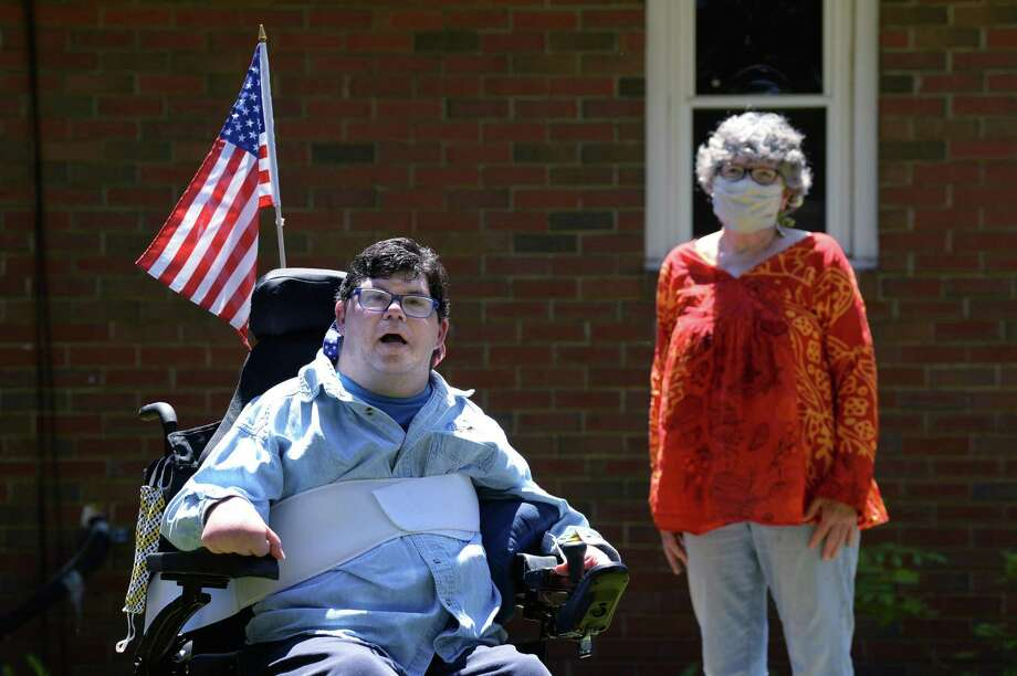 Penny Barsch, of Meriden, stands six feet away from her son, Shane Sessa, in the back yard of the group home where he lives in Portland. When Sessa, who has cerebral palsy, was hospitalized recently for surgery, Barsch was prohibited from accompanying him due to hospital restrictions in place since the onset of the COVID-19 pandemic. Photo: Cloe Poisson / CTMirror.org / Cloe Poisson