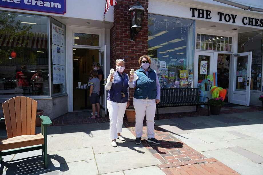 New Canaan's Chamber of Commerce Executive Director Tucker Murphy and Marketing Associate Laura Budd get cones from the Gofer Ice Cream shop at 103 Main Street soon after it opened on Wednesday, May 20. Photo: Grace Duffield / Hearst Connecticut Media