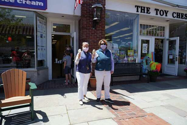 New Canaan's Chamber of Commerce Executive Director Tucker Murphy and Marketing Associate Laura Budd get cones from the Gofer Ice Cream shop at 103 Main Street soon after it opened on Wednesday, May 20.