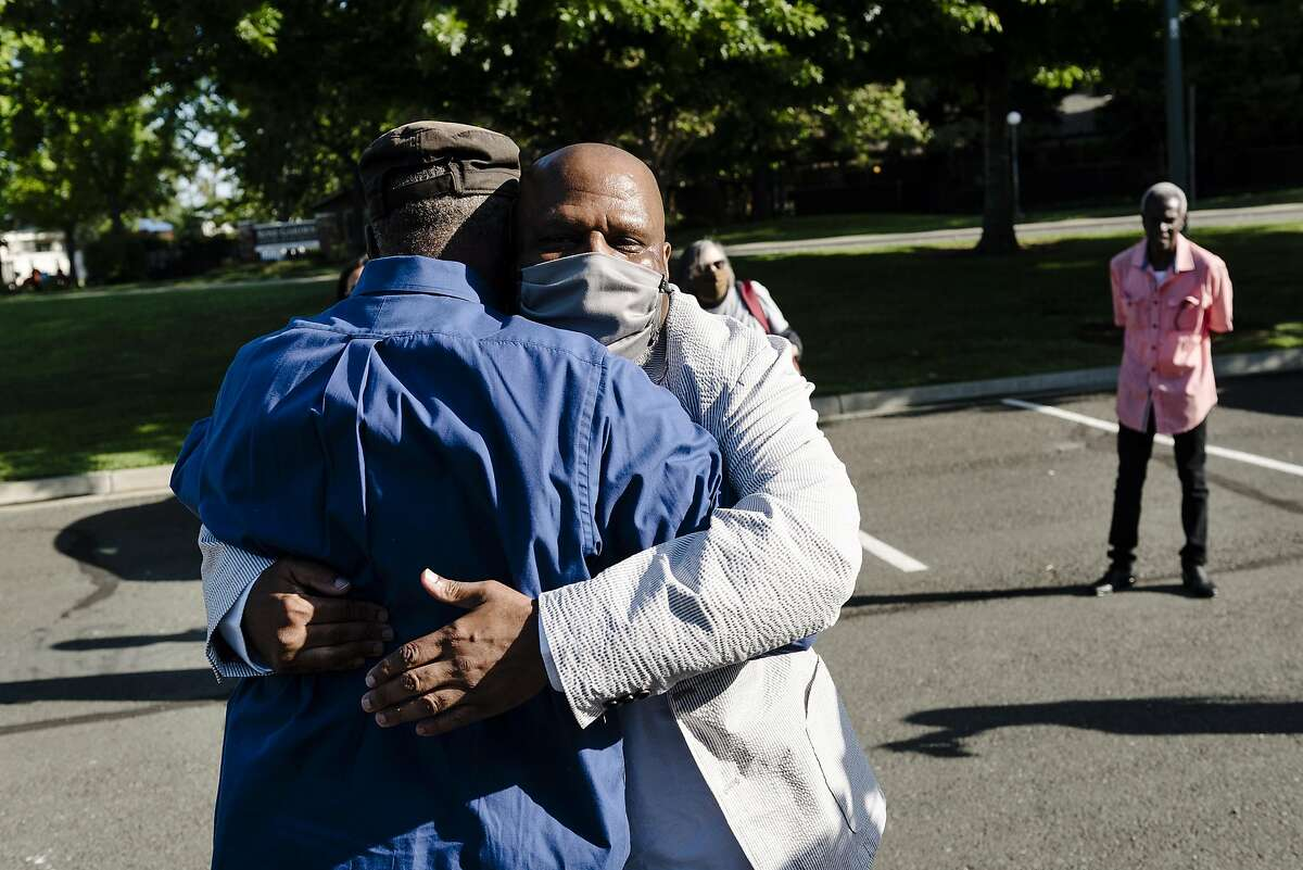 Paul Redd, center, hugs his cousin Danny Cotton after being released from the Department of Correction and Rehabilitation's California Medical Center after serving a total of 44 years in prison and more than 25 in solitary confinement, as family members gather at Al Patch Park in Vacaville, Calif, on Thursday, May 21, 2020.