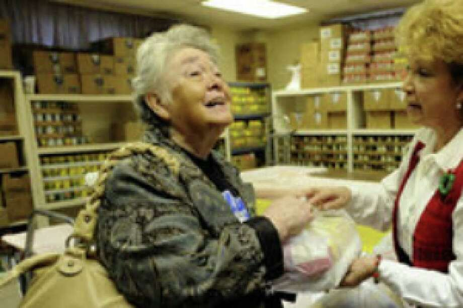 Josephine Flores (left) receives donated food from Lali Saucedo at the El Divino Salvador United Methodist Church food pantry. The pantry is one of four run by the Hispanic Religious Partnership for Community Health Inc.