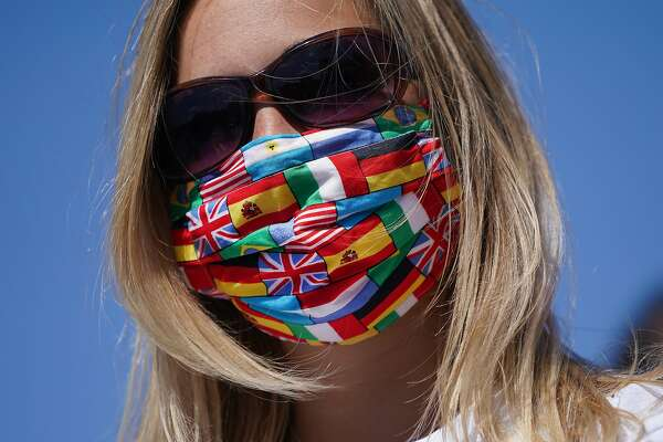 BERLIN, GERMANY - MAY 27: A protester wears a protective face mask with many nations' flags during a protest by travel agencies and tour bus operators during the coronavirus crisis on May 27, 2020 in Berlin, Germany. Approximately 300 tour buses took part in the protest and drove honking through the city center to demand government assistance due to heavy losses they are incurring during the pandemic. Similar protests took place in other cities in Germany today. (Photo by Sean Gallup/Getty Images)