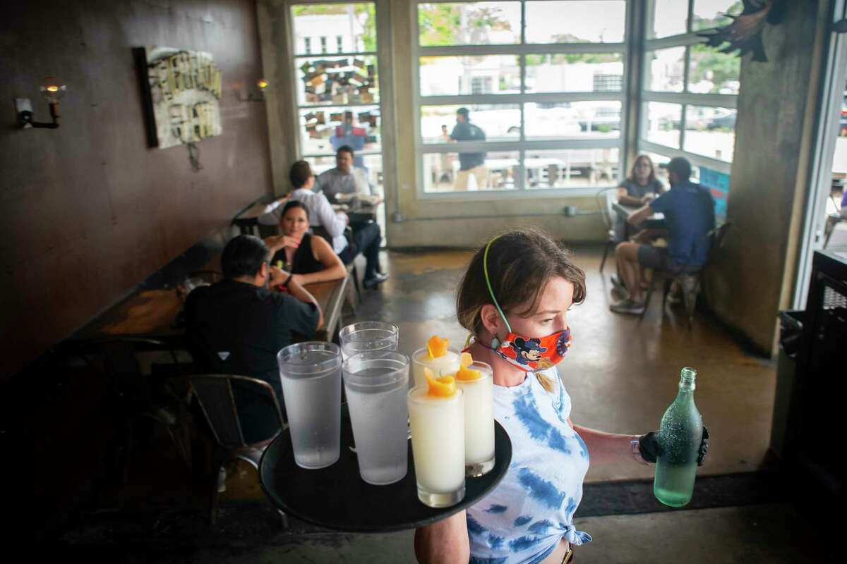 General manager Christina Ramey carries a tray of waters and frozen gin and tonics, Friday, May 22, 2020, at Eight Row Flint in Houston. Friday was the first day that bars were allowed to reopen in Texas.