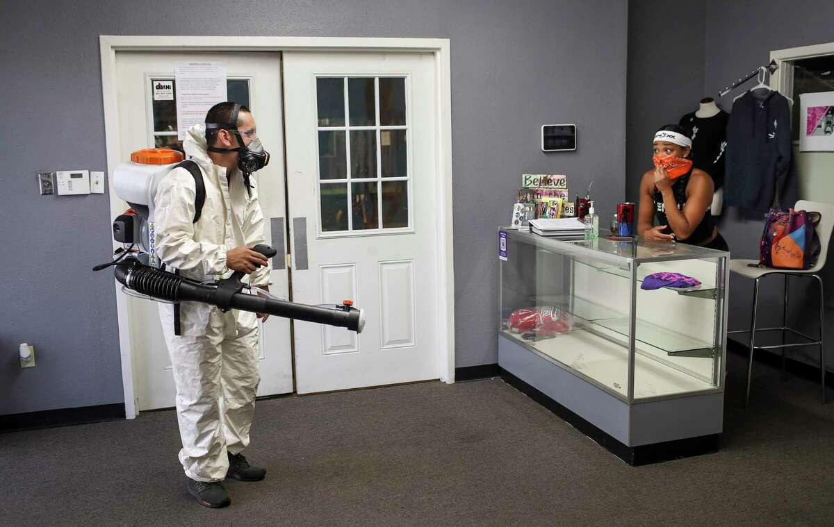 """Stephen Olivares, left, talks with Antanique Landry as he disinfects her gym Friday, May 15, 2020, in Houston. Landry, who said she isn't nervous but ready to reopen, is set to open her gym soon. """"It's actually a blessing that I was able to transition to virtual,"""" she said of operating during the shutdown. Olivares owns a gym maintenance company, and he said he started providing disinfecting services about a week before the shutdown, after about 80% of his clients asked for them."""