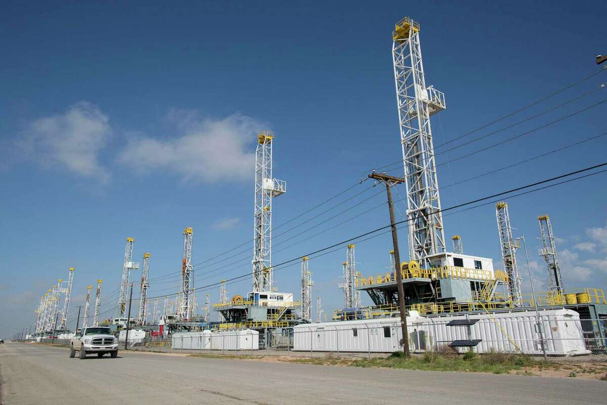 FILE - In this Monday, May 18, 2015, file photo, more than 30 oil drilling rigs stand idle in a Helmerich & Payne, Inc. yard along Groening Street in Odessa, Texas, as rig counts drop in the Permian Basin. Voters and economists hold sharply divergent views on U.S. economic growth. Economic recovery has occurred unevenly around the country. Falling oil prices for the past 18 months have brought widespread layoffs in the oil patch states, for example. But, according to a majority of economists surveyed by The Associated Press, the United States is resilient enough to defy the global economic slowdown and the sinking stock markets that have fanned fears of a new U.S. recession. (Courtney Sacco/Odessa American via AP, File)