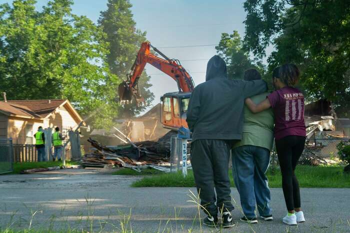 Breanna Green, 16, and Treyonne Green, 20, hug their grandmother, Annie Green, as they watch Annie's home of 43 years be demolished.