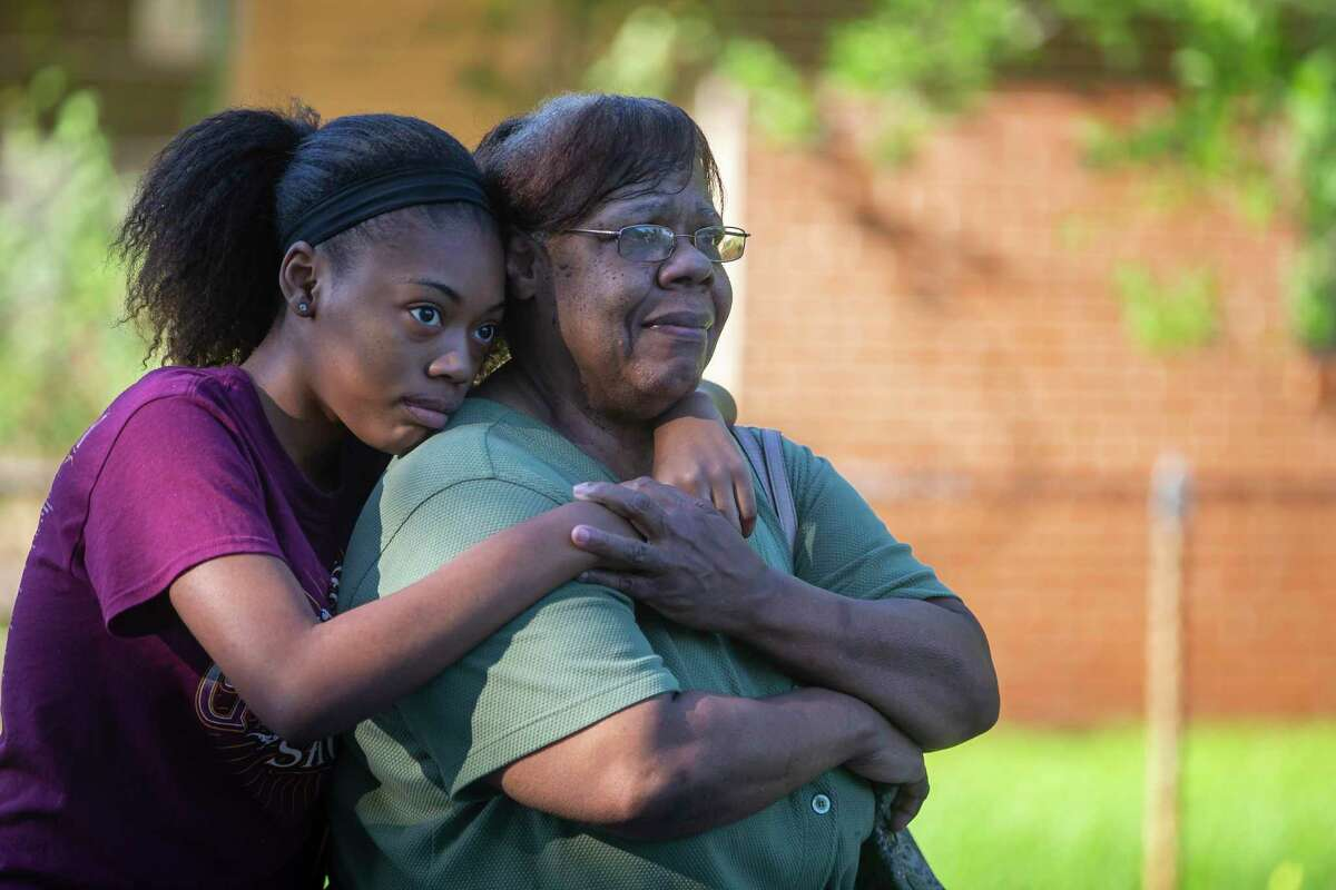 Breanna Green, 16, hugs her grandmother, Annie Green, as they watch Annie's home be demolished.