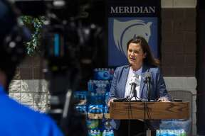 Gov. Gretchen Whitmer addresses members of the media, volunteers and community members during a press conference on flood recovery efforts Wednesday, May 27, 2020 at a donation center at Meridian Elementary in Sanford. (Katy Kildee/kkildee@mdn.net)