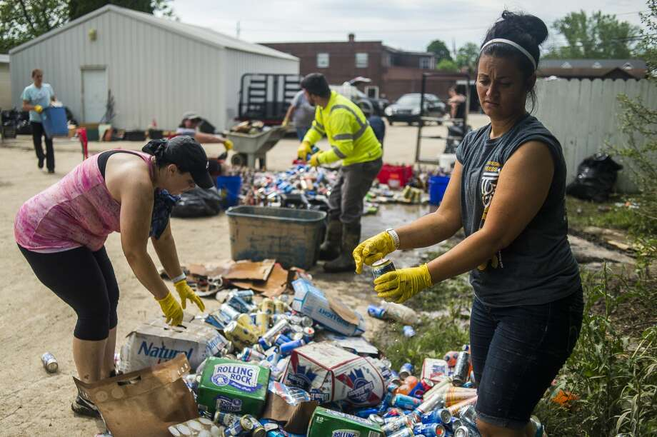 Veronica Gorman, right, empties beer cans as family members, employees and volunteers work to clear out the Poseyville Party Store of damaged merchandise and mud Wednesday, May 27, 2020 in Midland. (Katy Kildee/kkildee@mddn.net) Photo: (Katy Kildee/kkildee@mdn.net)