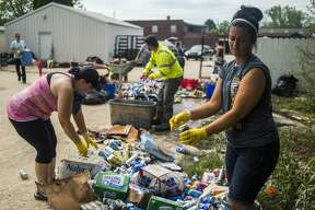 Veronica Gorman, right, empties beer cans as family members, employees and volunteers work to clear out the Poseyville Party Store of damaged merchandise and mud Wednesday, May 27, 2020 in Midland. (Katy Kildee/kkildee@mddn.net)