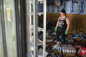 Lexis Miller looks around at merchandise strewn about the floor inside Poseyville Party Store while family members, employees and volunteers work to clear the store of damaged merchandise and mud Wednesday, May 27, 2020 in Midland. (Katy Kildee/kkildee@mddn.net)