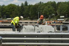 MDOT workers continue to shore up the U.S. 10 bridge in Sanford May 27, 2020 after erosion during last week's flood removed much of the soil surrounding its foundation. (Katy Kildee/kkildee@mdn.net)