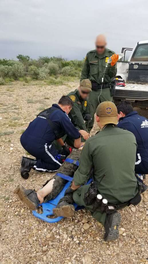 U.S. Border Patrol agents render aid to a woman who was lost at a ranch with her two children. She was airlifted to a local hospital for further medical treatment. Photo: Courtesy Photo /U.S. Border Patrol