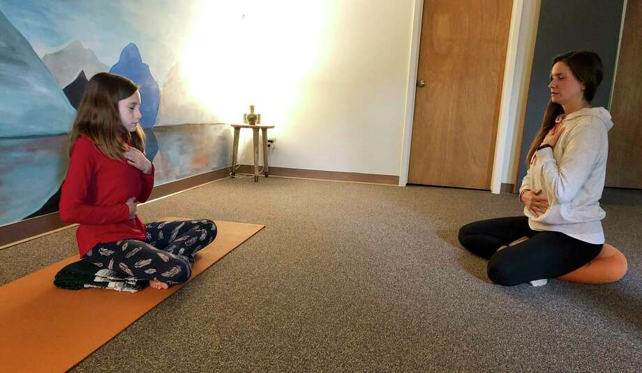 Erin Schifferli and her 12-year-old daughter, Aeva, demonstrate a stress-relieving breathing exercise in her yoga studio in East Aurora, N.Y. Photo: Carolyn Thompson / Associated Press / Ap