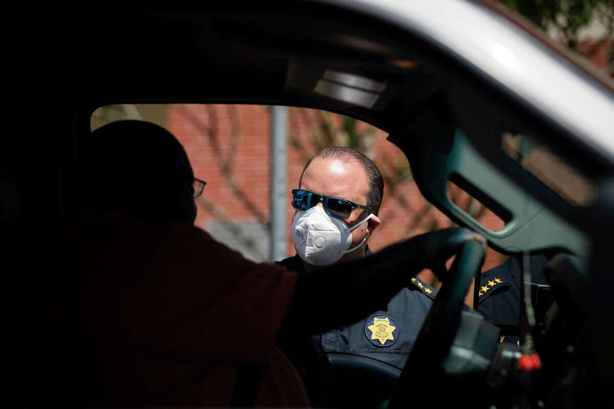 Constable Alan Rosen talks to a man at a drive-through that is providing masks, gloves and a box with groceries to Acres Homes area on Tuesday, April 14, 2020, in Houston.