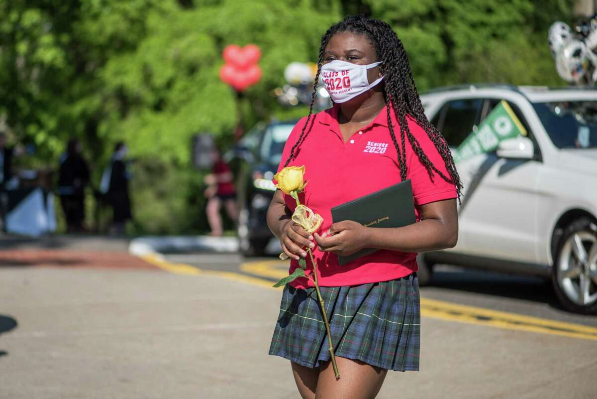 Greenwich Academy senior A. J. Bonnet walks with yellow rose and diploma in hand back to her car during the car parade and graduation ceremony held on Monday. Students were driven through the school's traffic circle by family members, while faculty waved on from the driveway. They got out one by one to receive their diploma and pose for two pictures, including one with a cutout of their head of school, Molly King.