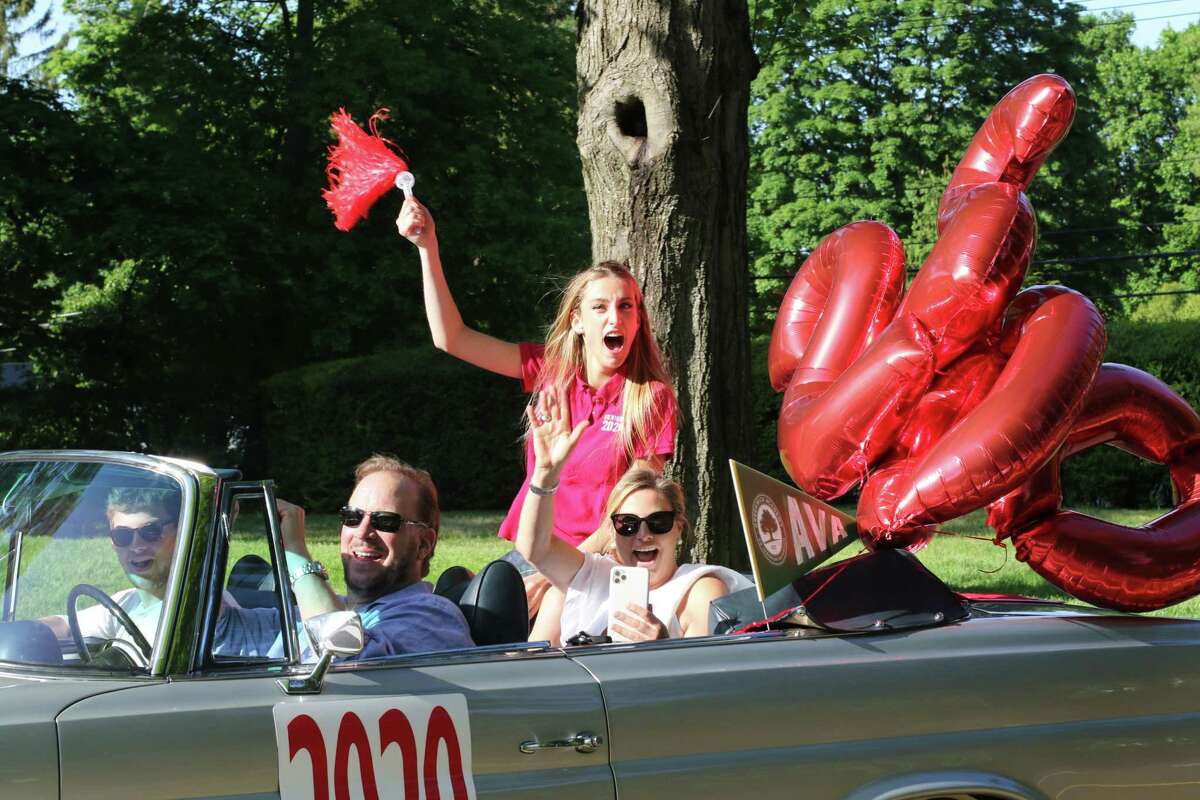 Ava Darrin, an alumna of Greenwich Academy as of Monday, celebrates from her family's convertible with the top down. Students were driven through the school's traffic circle by family members, and got out to receive their diplomas and pose for pictures.