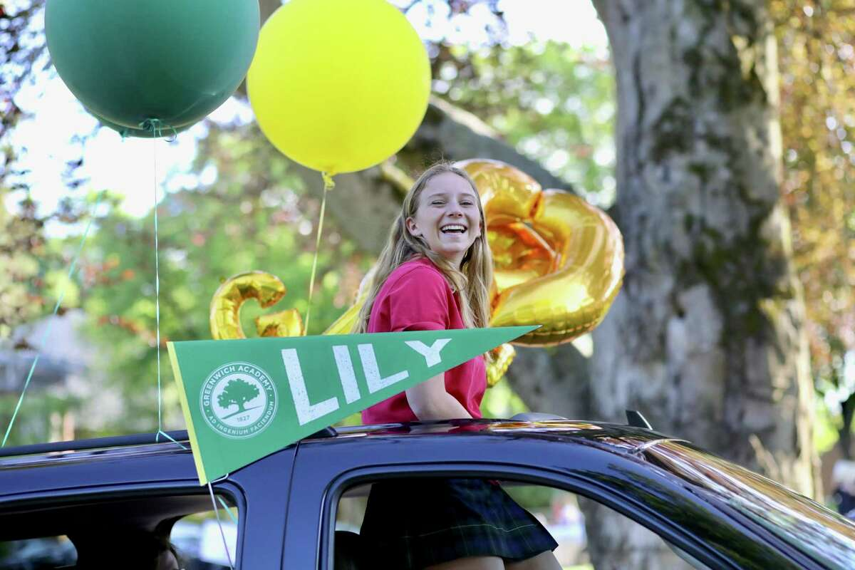 Lily Shore peeks her head out of the sun roof of her family's car during the Greenwich Academy graduation car parade, held Monday. Students were driven through the school's traffic circle by family members, while faculty waved on from the driveway. They got out one by one to receive their diploma and pose for two pictures, including one with a cutout of their head of school, Molly King.