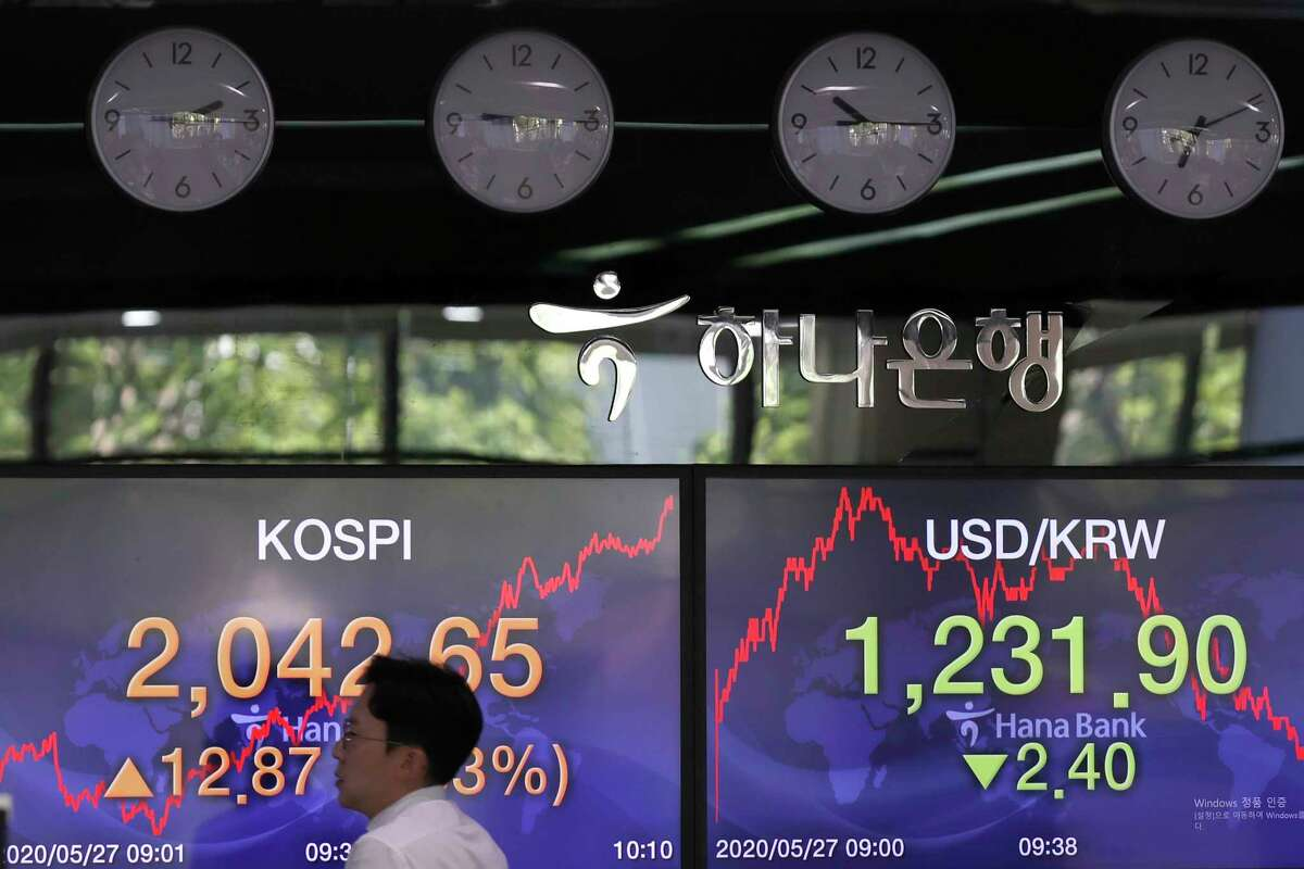 A currency trader walks by the screens showing the Korea Composite Stock Price Index (KOSPI), left, and the foreign exchange rate between U.S. dollar and South Korean won at the foreign exchange dealing room in Seoul, South Korea, Wednesday, May 27, 2020. Major Asian stock markets have declined as US-Chinese tension over Hong Kong competes with optimism about recovery from the coronavirus pandemic. (AP Photo/Lee Jin-man)